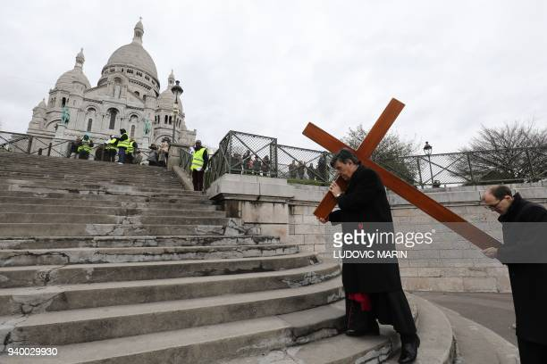 Archbishop of Paris Michel Aupetit carries a cross during a Stations of the Cross procession on Good Friday in front of Sacre Coeur Basilica on...