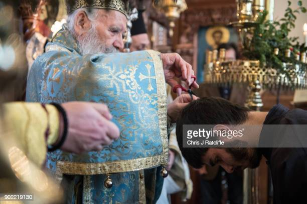 Archbishop of Thyteiri and Great Britain cuts the hair of Stylianos Vogiatzis as he is made a Reader during a traditional Greek Orthodox blessing at...