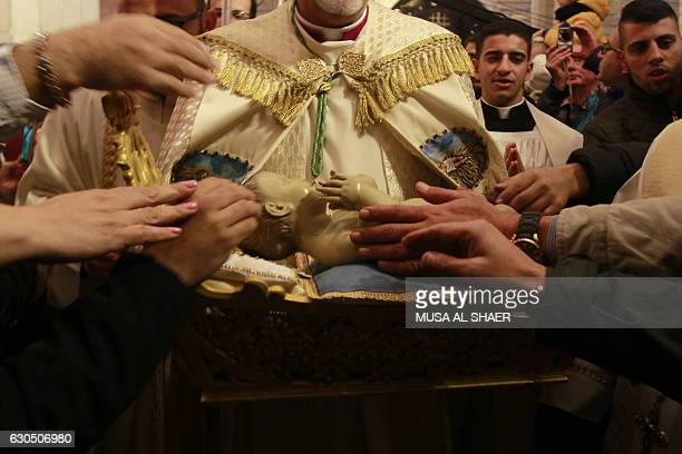 Archbishop Pierbattista Pizzaballa apostolic administrator of the Latin Patriarch of Jerusalem holds the Baby Jesus in Saint Catherine's Church at...