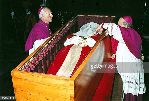 Archbishop Stanislaw Dsiwisz places a white veil over the face of late Pope John Paul II as Archbishop Piero Marini looks on prior to closing the...