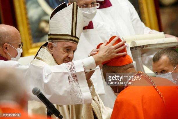 Archbishop Wilton Gregory of Washington receives his biretta from Pope Francis as he is created Cardinal during a consistory to create 13 new...