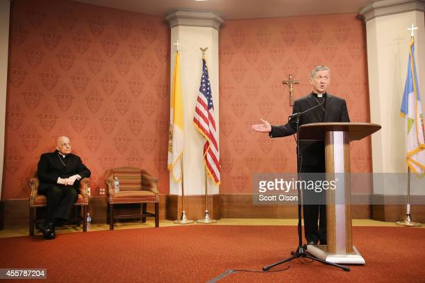 ArchbishopElect Blase Cupich speaks to the press as Francis Cardinal George listens on September 20 2014 in Chicago Illinois Cupich who served as...