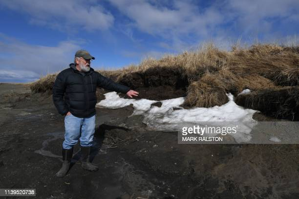 Archeologist Dr Rick Knecht shows a site threatened by climate change erosion caused by high temperatures that melts permafrost tundra and washes...