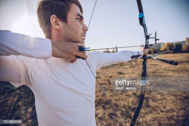 archer aiming at target - curved arrows stock photos and pictures