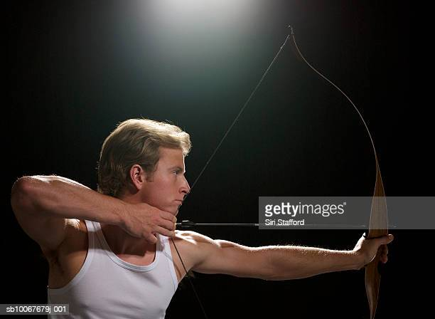Archer aiming bow and arrow, on black background