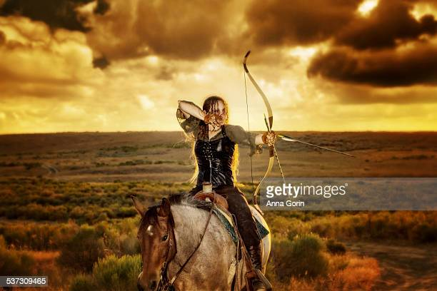Archer on horseback in medieval garb at sunset