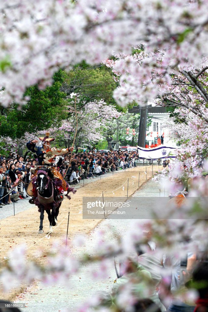 Archer on the running horseback aims at a target under fully-bloomed cherry blossoms during a cherry blossom festival at Mihashira Shrine on March 31, 2013 in Yanagawa, Fukuoka, Japan.