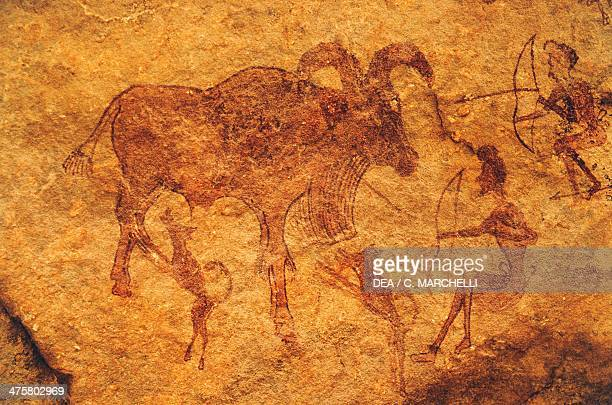 Archers dogs and a hoofed animal cave painting Tassili n'Ajjer Algeria