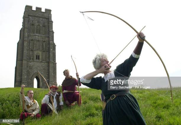 Archers in Tudor costume stand in front of the Glastonbury Tor from back Philip Head Richard Head and Hector Cole watch Lindsay Head take aim at the...