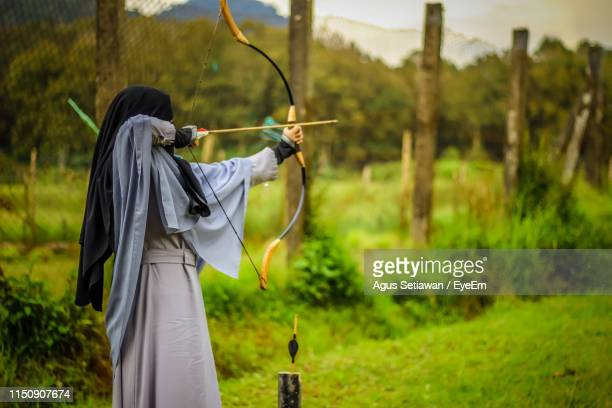 archery aiming bow against trees - aiming stock pictures, royalty-free photos & images