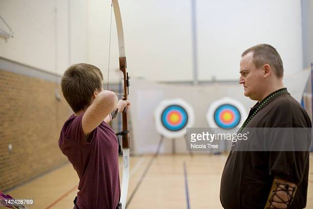 archery coach teaching a young archer to shoot. - aiming stock pictures, royalty-free photos & images