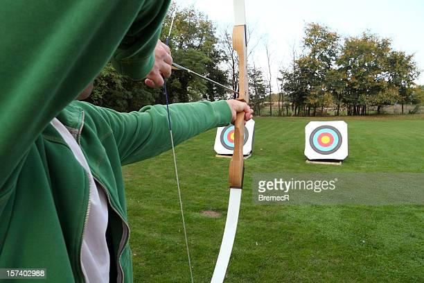Archery firing at targets on a grass field