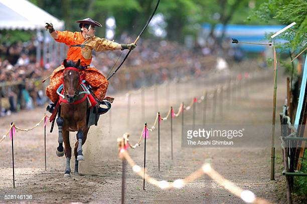 Archery releases the arrow during the 'Yabusame' horseback archery ritual at Shimogamo Jinja Shrine on May 3 2016 in Kyoto Japan