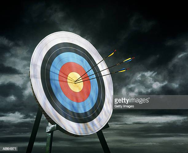 Archery target with arrows, dark clouds in background