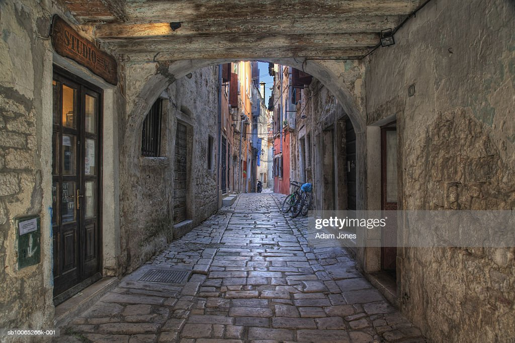 Arches over cobblestone street and wooden doorway : Foto stock