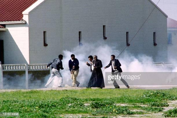 Archibishop Desmond Tutu assited by Jakes Gerwel rector of the University of the Western Cape try to escape teargas fired by police on August 23 1989...
