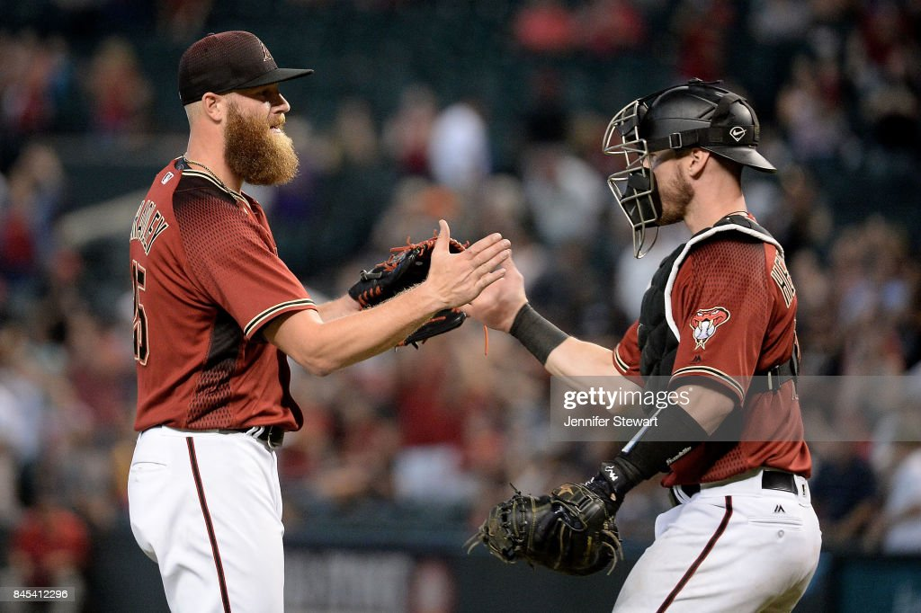 Archie Bradley #25 and Chris Herrmann #10 of the Arizona Diamondbacks high five after closing out the MLB game against the San Diego Padres at Chase Field on September 10, 2017 in Phoenix, Arizona.