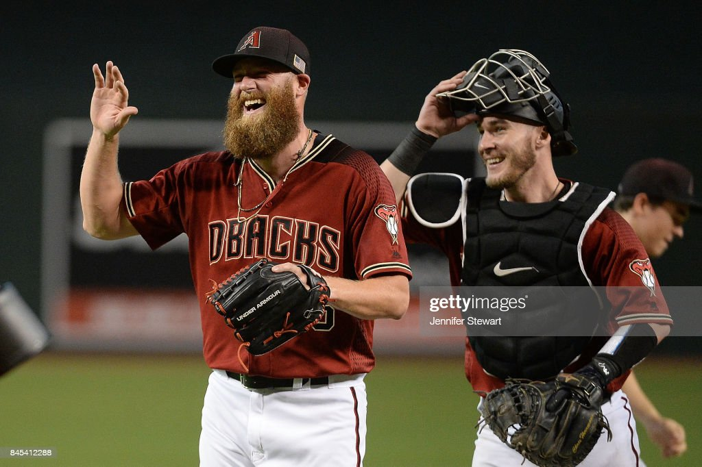 Archie Bradley #25 and Chris Herrmann #10 of the Arizona Diamondbacks smile after closing out the MLB game against the San Diego Padres at Chase Field on September 10, 2017 in Phoenix, Arizona.