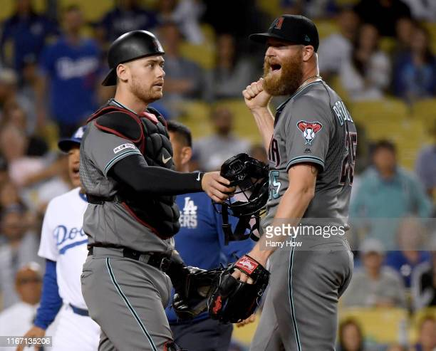 Archie Bradley of the Arizona Diamondbacks is restrained by Carson Kelly after his pitch hit AJ Pollock of the Los Angeles Dodgers in the hands...