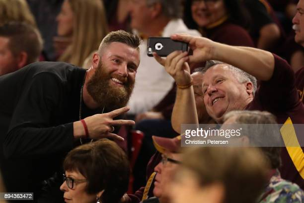 Archie Bradley of the Arizona Diamondbacks poses for a selfie with a fan during the second half of the college basketball game between the Arizona...