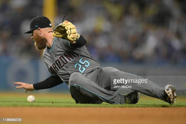 Archie Bradley of the Arizona Diamondbacks scrambles for a ball hit by Justin Turner of the Los Angeles Dodgers in the eighth inning at Dodger...