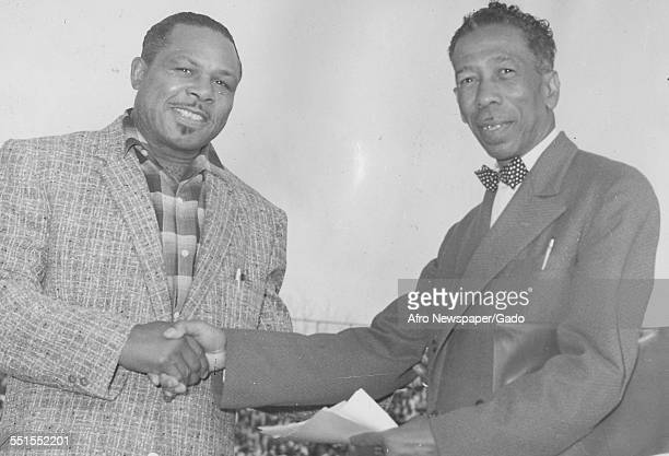 Archie Moore AfricanAmerican professional boxer and the Light Heavyweight World Champion shaking hands with a man 1955