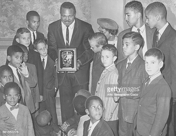 Archie Moore AfricanAmerican professional boxer and the Light Heavyweight World Champion giving out awards to young people November 4 1961