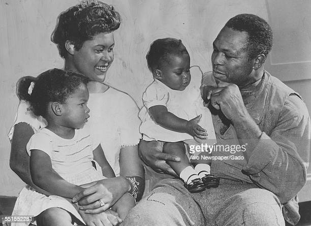 Archie Moore AfricanAmerican professional boxer and the Light Heavyweight World Champion with his wife and two young daughters November 6 1960