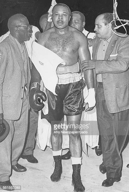 Archie Moore AfricanAmerican professional boxer and the Light Heavyweight World Champion being escorted from the ring in the match with Pete...