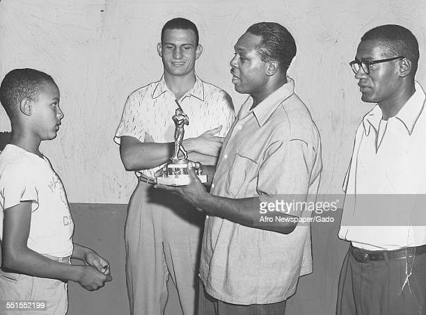 Archie Moore American professional boxer and the Light Heavyweight World Champion awarding a trophy to a promising young basketball player 1955