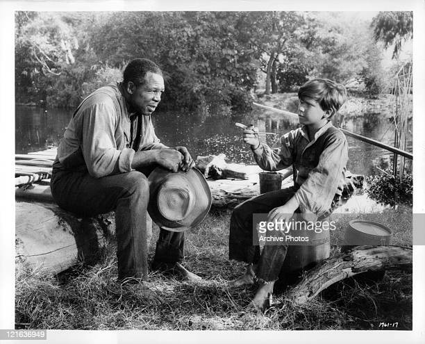 Archie Moore And Eddie Hodges sit on stump talking in a scene from the film 'Adventures of Huckleberry Finn' 1960