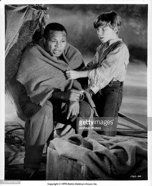 Archie Moore being wrapped in a blanket by Eddie Hodges in a scene from the film 'Adventures of Huckleberry Finn' 1960