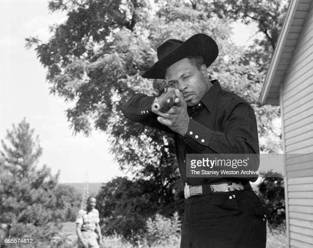 Archie Moore dressed as a cowboy aims his rifle at the camera at this training camp in North Adams New York circa 1955
