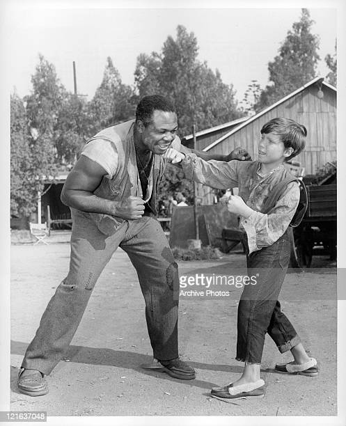Archie Moore giving Eddie Hodges pointers in boxing in a scene from the film 'Adventures of Huckleberry Finn' 1960