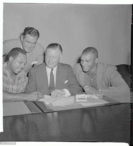 Archie Moore of San Diego California light heavyweight title holder signs his contract here as Robert K Christenberry Chairman of the New York State...