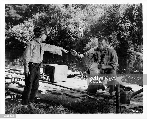 Archie Moore pleads with Huck played by Eddie Hodges to travel with him down the Mississippi in a scene from the film 'The Adventures Of Huckleberry...
