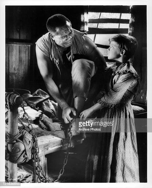 Archie Moore rest leg on table top as Eddie Hodges assists with removing shackles from his leg in a scene from the film 'Adventures of Huckleberry...
