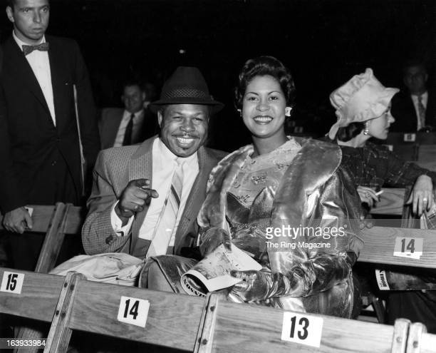 Archie Moore sits with his wife as they watch Carmen Basilio win the fight against Ray Robinson at Yankee Stadium in New York New York