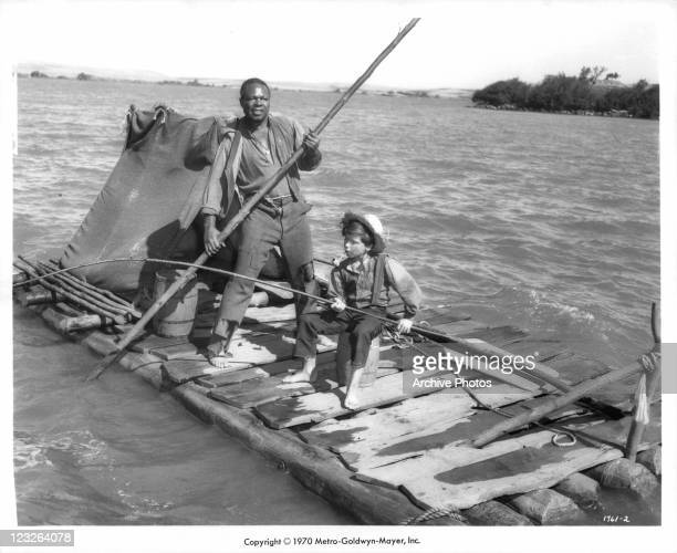 Archie Moore steering raft while Eddie Hodges fishes in a scene from the film 'The Adventures Of Huckleberry Finn' 1960