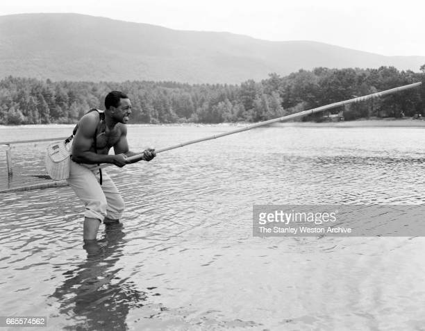 Archie Moore strengthening his forearms by using a bamboo fishing rod at his camp in North Adams New York circa 1955