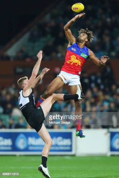 Archie Smith of the Lions taps the ball away from Jackson Trengove of the Power during the round 13 AFL match between the Port Adelaide Power and the...