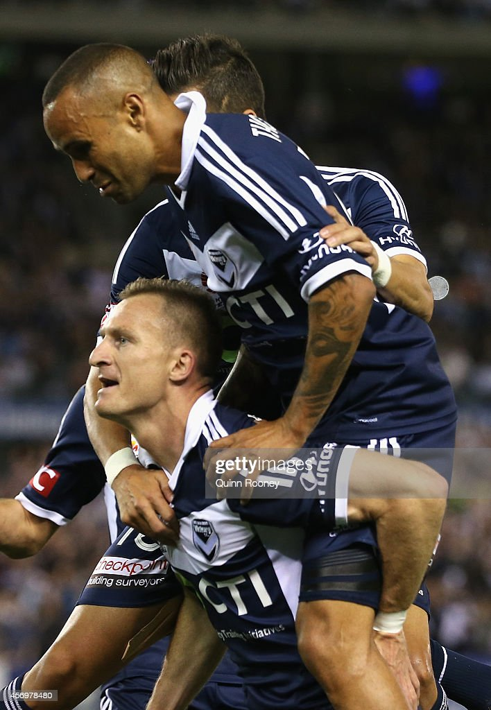 Archie Thompson jumps on Besart Berisha of the Victory after he scores a goal during the round one A-League match between Melbourne Victory and the Western Sydney Wanderers at Etihad Stadium on October 10, 2014 in Melbourne, Australia.