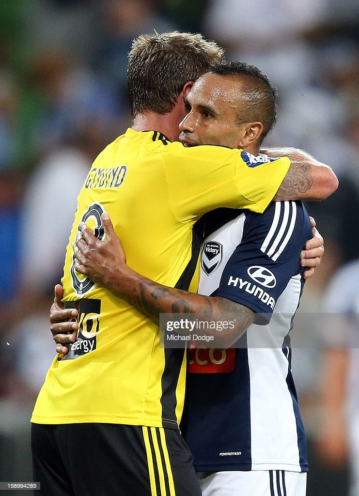 Archie Thompson of the Melbourne Victory (R) hugs Ben Sigmund of the Wellington Phoenix after the round 15 A-League match between the Melbourne Victory and Wellington Phoenix at AAMI Park on January 5, 2013 in Melbourne, Australia.