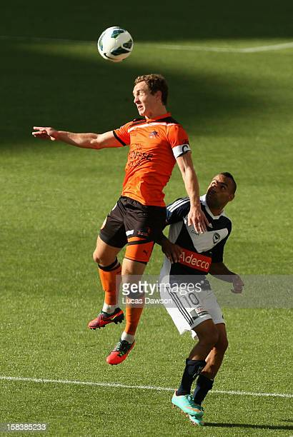 Archie Thompson of the Victory and Matthew Smith of the Roar contest for the ball during the round 11 ALeague match between the Melbourne Victory and...
