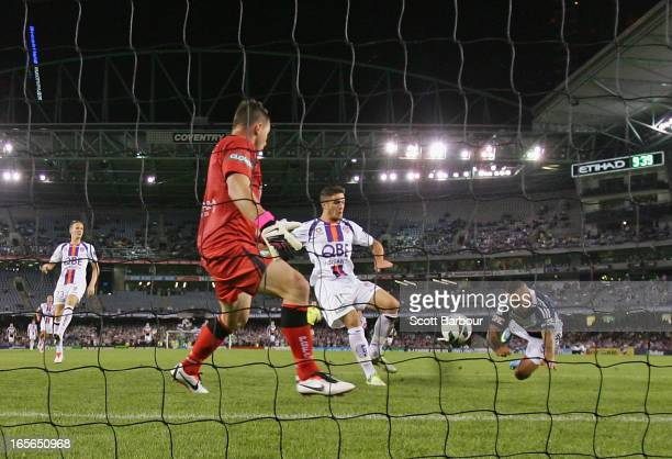 Archie Thompson of the Victory beats goalkeeper Daniel Vukovic of the Glory to score his teams second goal in extra time during the ALeague...