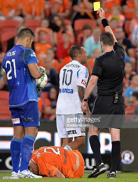 Archie Thompson of the Victory is given a yellow card by referee Ben Williams during the round 26 ALeague match between the Brisbane Roar and...