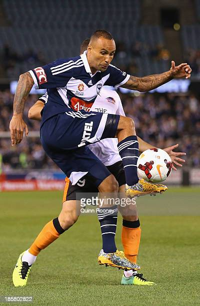 Archie Thompson of the Victory kicks the ball infront of Jack Hingert of the Roar during the round three ALeague match between Melbourne Victory and...