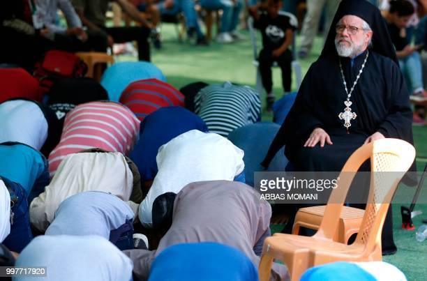 Archimandrite Abdullah Yulio parish priest of the Melkite Greek Catholic church in Ramallah sits amongst Muslim worshippers during Friday prayers...