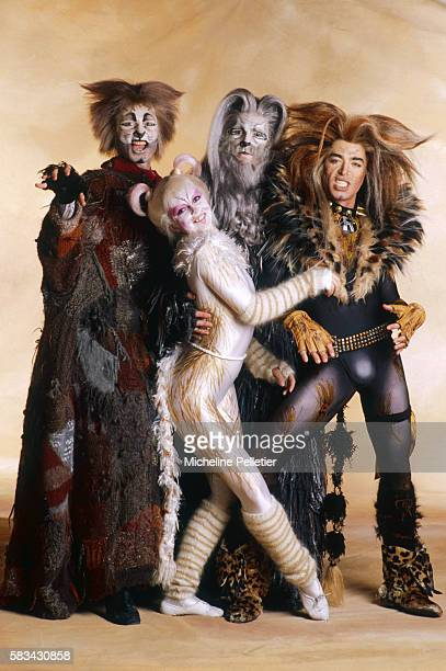 Arching her back in true feline fashion an actor in the musical Cats poses for a photo along with three other cast members decked out in all their...