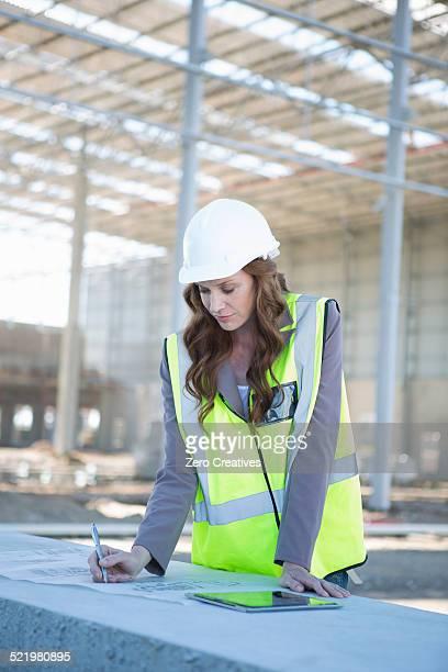 Architect adjusting blueprint on construction site